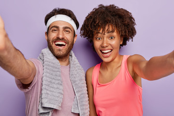 Sporty couple makes selfie after fitness exercise, smile broadly, express good emotions, wear casual clothes, keep hands extended, lead healthy lifestyle, isolated over purple wall. Workout, training