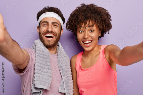 fototapeta na ścianę Sporty couple makes selfie after fitness exercise, smile broadly, express good emotions, wear casual clothes, keep hands extended, lead healthy lifestyle, isolated over purple wall. Workout, training