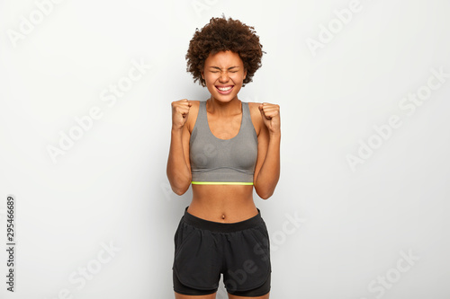 Energized sporty woman rejoices winning, raises clenched fists, smiles broadly, wears sport bra , smiles broadly, isolated over white background, awaits for something Tablou Canvas