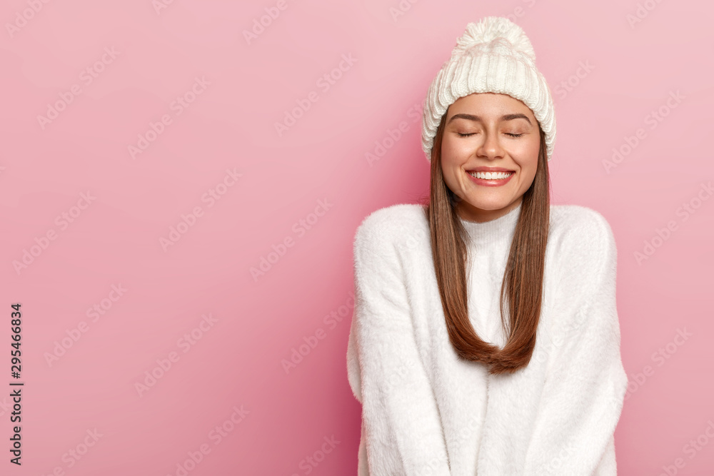 Fototapety, obrazy: Horizontal shot of pretty young female with dark hair, keeps eyes shut, imagines pleasant moment, smiles pleasantly, shows white perfect teeth, enjoys comfort in new bought sweater, warm hat