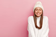 canvas print picture - Horizontal shot of pretty young female with dark hair, keeps eyes shut, imagines pleasant moment, smiles pleasantly, shows white perfect teeth, enjoys comfort in new bought sweater, warm hat