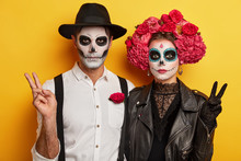 Indoor Shot Of Serious Woman And Man In Special Scary Costumes, Make Peace Victory Gesture, Have Vivid Makeup For Looking Horrible, Celebrate Traditional Holiday In Mexico. Costume Party. Terrible Day
