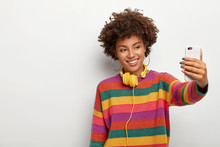 Cheerful Dark Skinned Woman With Dark Curly Hair, Makes Selfie Via Smartphone, Dressed In Colorful Sweater, Smiles Gently, Being Music Meloman, Stands Against White Background, Blank Space Aside