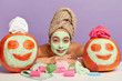 canvas print picture - Lovely relaxed woman applies rejuvenation mask after taking bath at home, poses at table with all necessary things for beauty treatments, has clean fresh skin, two pumpkins with drawn faces and towels