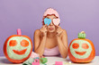 Leinwanddruck Bild - Image of young female cares about skin, covers both eyes with two heart shaped sponges, wears soft shower cap, has beauty treatments, applies clay facial mask on pumpkins, prepares for Halloween