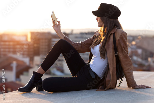 Obraz na plátně Pretty young woman taking a selfie with mobile phone while sitting on the rooftop