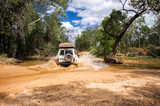 Fototapeta Sawanna - Western Australia – Flooded Outback gravel road with 4WD car crossing the waterhole with splashing muddy water at the savanna