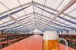 Leinwanddruck Bild - Fertiges und noch leeres Festzelt für das Oktoberfest mit, auf einem Holztisch steht ein Glas Bier