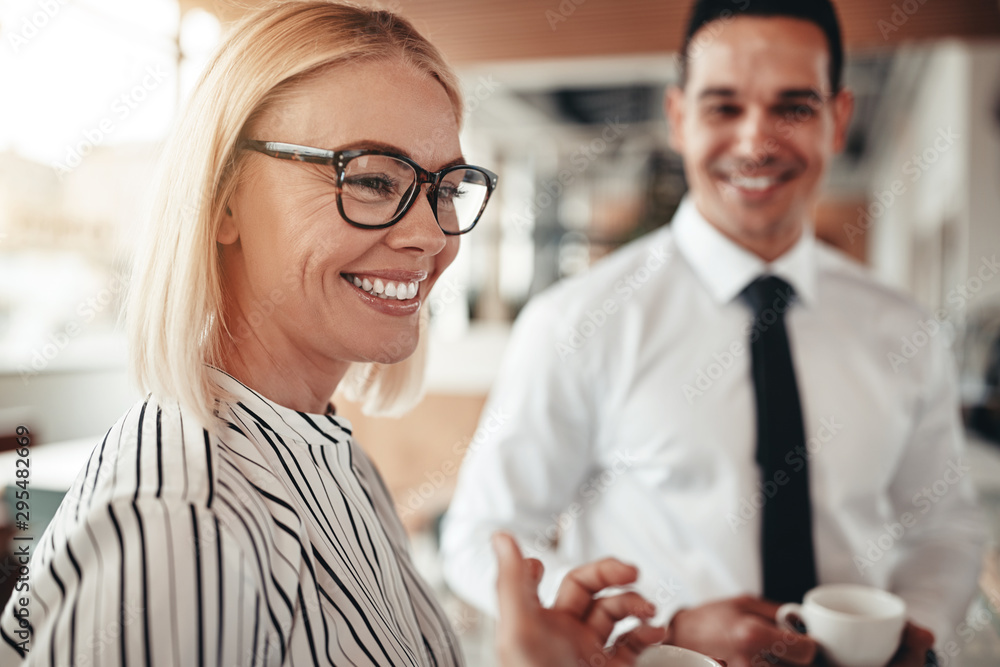 Fototapeta Smiling businesswoman talking with colleagues over coffee in an