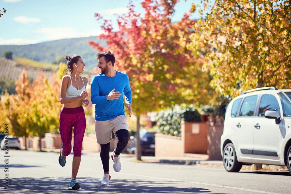 Fototapety, obrazy: Man and woman enjoying at jogging at city