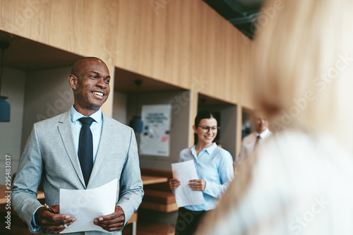 Fototapeta Smiling African American businessman walking with colleagues in obraz