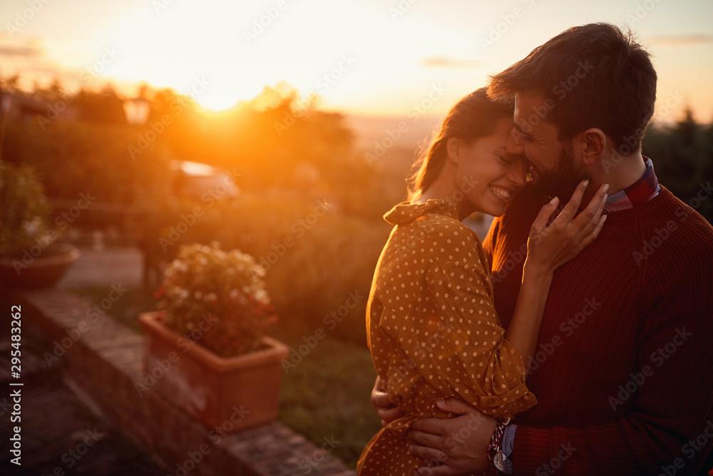 Fototapeta romantic man and woman at sunset. Smiling man and woman is enjoying sunset