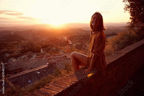 Fotografiet  woman at sunset. Smiling woman is enjoying sunset