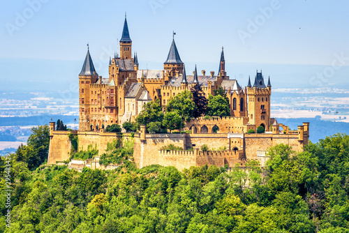 Hohenzollern Castle on mountain top close-up, Germany. Fairytale castle is famous landmark near Stuttgart. Scenic view of mount Burg Hohenzollern in forest.