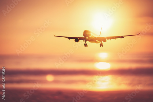 Garden Poster Airplane Airplane flying over tropical beach with smooth wave and sunset sky abstract background.