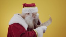 Happy Santa Claus Holding Vintage Paper On Yellow Background. Merry Christmas And New Year's Eve Concept. Copy Space. Difficulty Reading. Ugly Handwriting.
