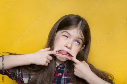 Photo little girl makes a grimace, portrait of young girl isolated on yellow backgroun
