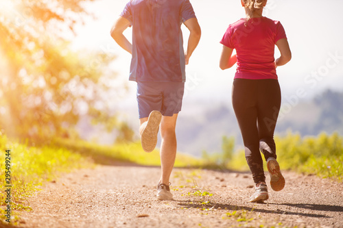 Leinwand Poster  young couple jogging on sunny day at nature
