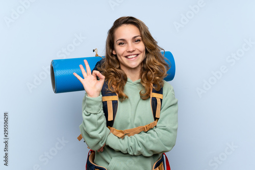 Fotomural  Young blonde hiker girl over isolated blue background showing ok sign with finge