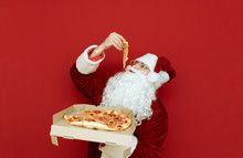 Hungry Man In A Santa Claus Costume Stands With A Delivery Box Of Pizza On A Red Background And Eats A Piece. Santa Loves To Eat Pizza. Christmas Concept. Copy Space