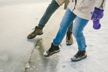 Trying The Danger Of The Foot, Testing The Thin Ice Near The Shore. A Pair Of Lovers Walk With A Walk Along A Frozen Lake To Press Foot On The Ice
