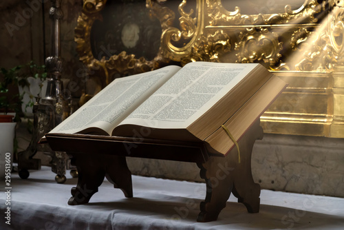 Foto Open bible illuminated by sunbeams on an altar