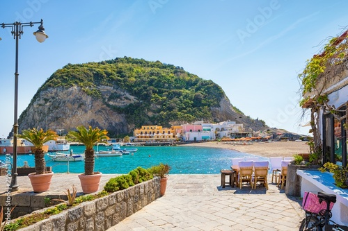 Fotobehang Blauwe hemel Beautiful coast of village Sant'Angelo, giant green rock in blue sea near Ischia Island, Italy.