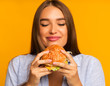 Happy Girl Eating Burger Standing, Studio Shot