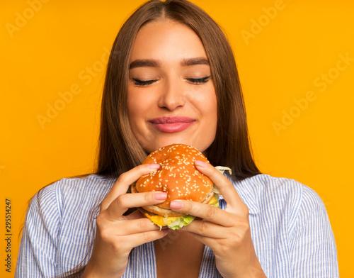 Valokuvatapetti Happy Girl Eating Burger Standing, Studio Shot