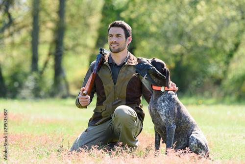Fotografía huntsman with gun kneeling by his dog