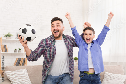 Emotional dad and son cheering with football ball, celebrating goal at home Canvas Print