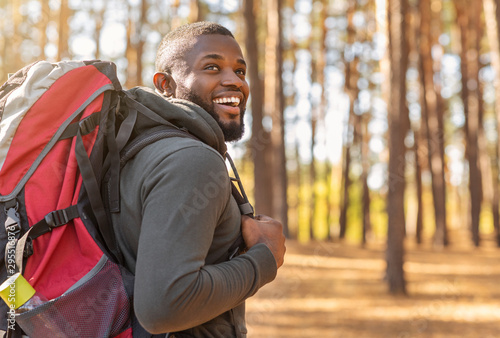 Fotografía African man wearing backpack standing on forest trail