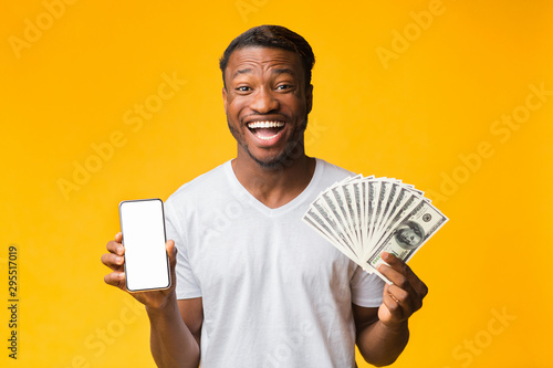 Foto  Afro Guy Holding Smartphone And Money Standing On Yellow Background