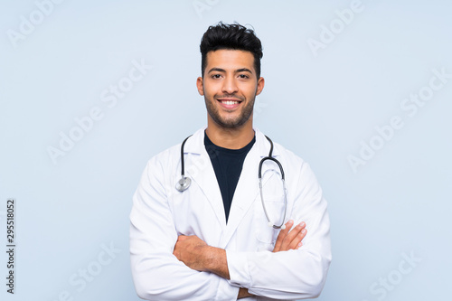 Young doctor man over isolated blue wall smiling a lot Wallpaper Mural