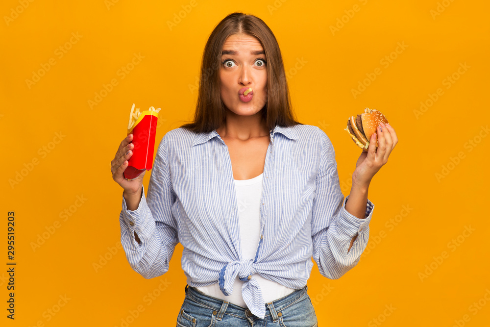 Fototapety, obrazy: Surprised Woman Eating Burger And French Fries, Studio Shot