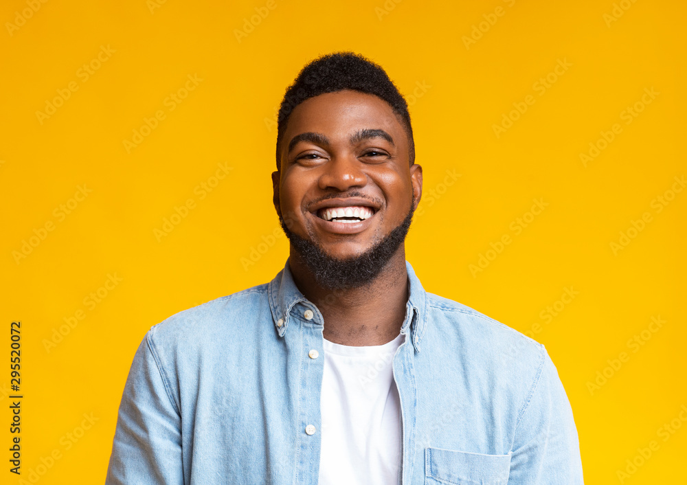 Fototapeta Portrait of young laughing african american guy over yellow background