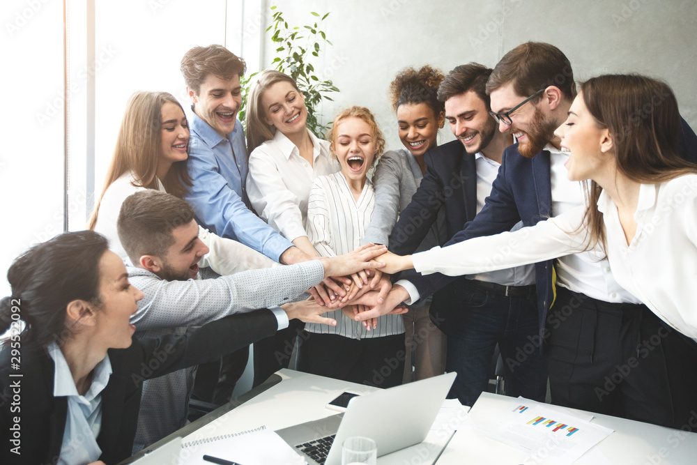 Fototapeta Happy business team joining hands together, celebrating success