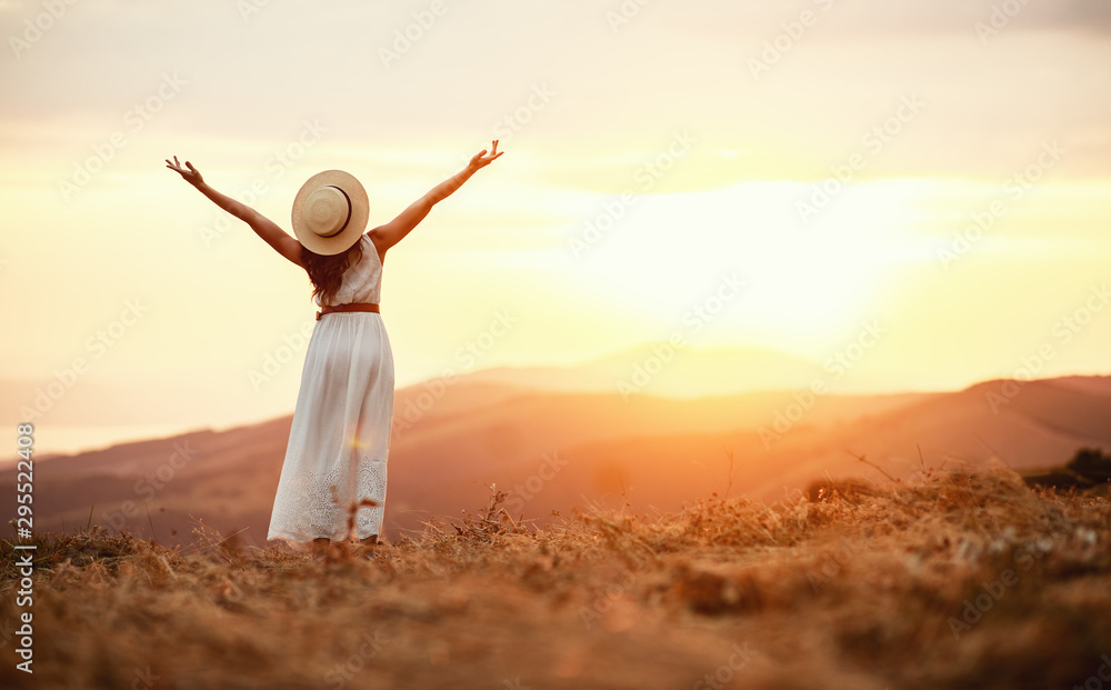 Fototapeta Happy woman standing with her back on sunset in nature  .