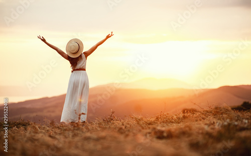 Obraz Happy woman standing with her back on sunset in nature  . - fototapety do salonu