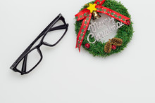 Flat Lay Top View Of Eyeglasses And Merry Christmas Sign With Copy Space. Merry Christmas And Happy New Year Background Concept.
