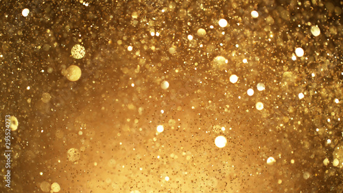 Photo Abstract golden glittering background with blur dots.