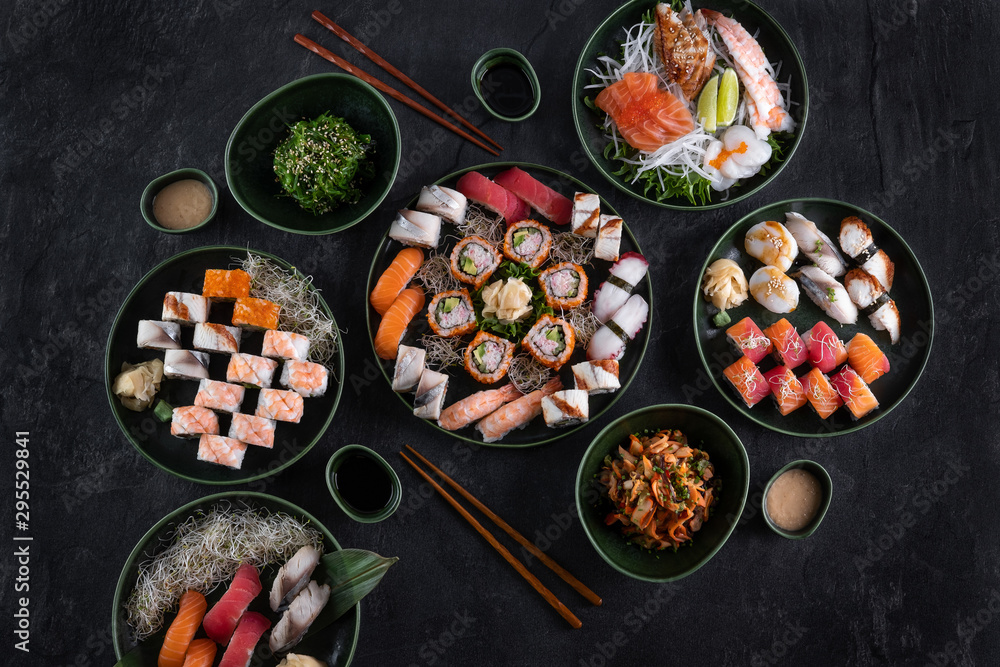 Fototapety, obrazy: Assorted sushi set served on dark stone slate background. Top view of wakame salad, seafood,various maki rolls, sashimi and nigiri with caviar, prawn, scallop, octopus, salmon, eel, mackerel and tuna