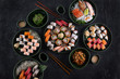 Assorted sushi set served on dark stone slate background. Top view of wakame salad, seafood,various maki rolls, sashimi and nigiri with caviar, prawn, scallop, octopus, salmon, eel, mackerel and tuna
