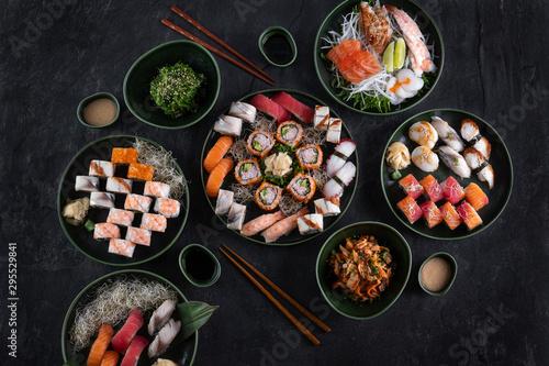 Fototapeta Assorted sushi set served on dark stone slate background. Top view of wakame salad, seafood,various maki rolls, sashimi and nigiri with caviar, prawn, scallop, octopus, salmon, eel, mackerel and tuna obraz