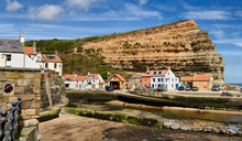 Red Cliff Of Jurassic Strata At The Mouth Of Staithes Beck Emptying Into The North Sea At Staithes Harbour North York Moors National Park England