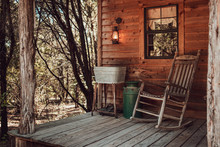 Rocking Chair On The Cabin Front Porch In The Woods