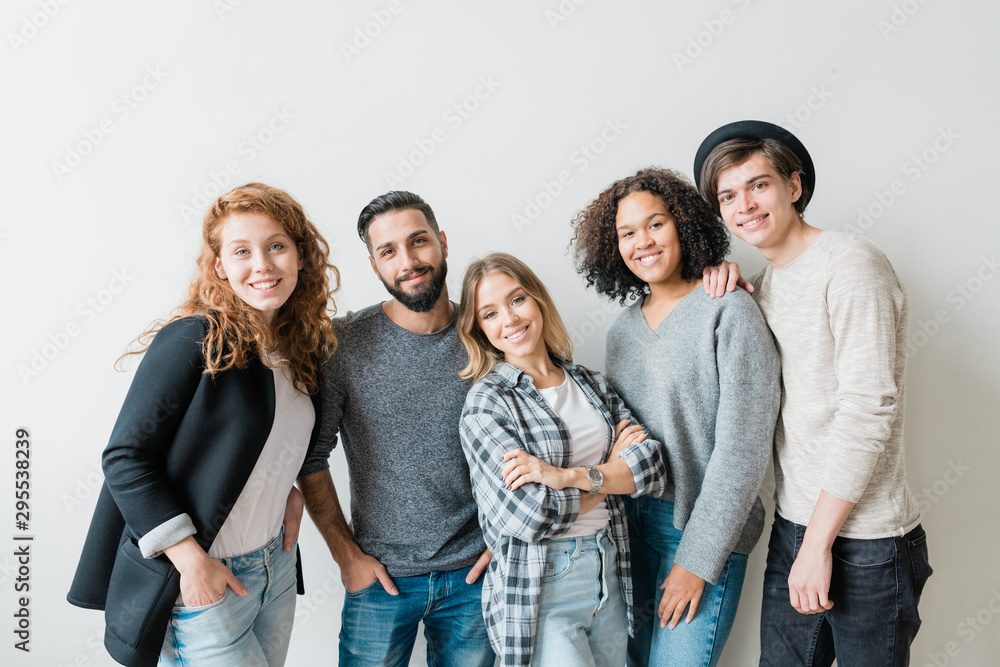 Fototapeta Smiling guys and girls in casualwear standing by white wall in front of camera
