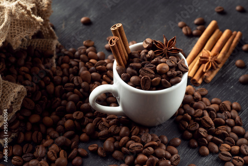White cup full of coffee beans cinnamon bag spills out coffee stars anise star anise on a dark background