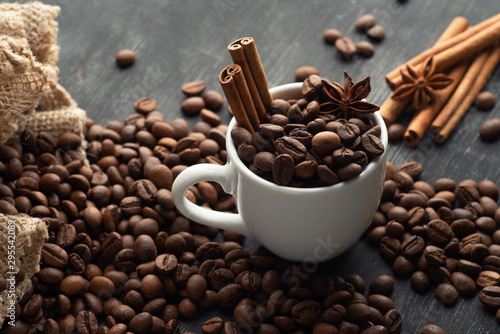 Tuinposter Cafe White cup full of coffee beans cinnamon bag spills out coffee stars anise star anise on a dark background