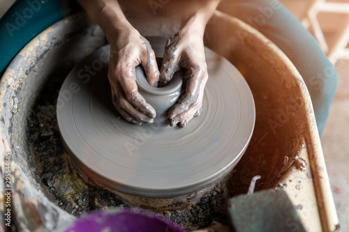 Woman making ceramic work with potter's wheel Fotobehang